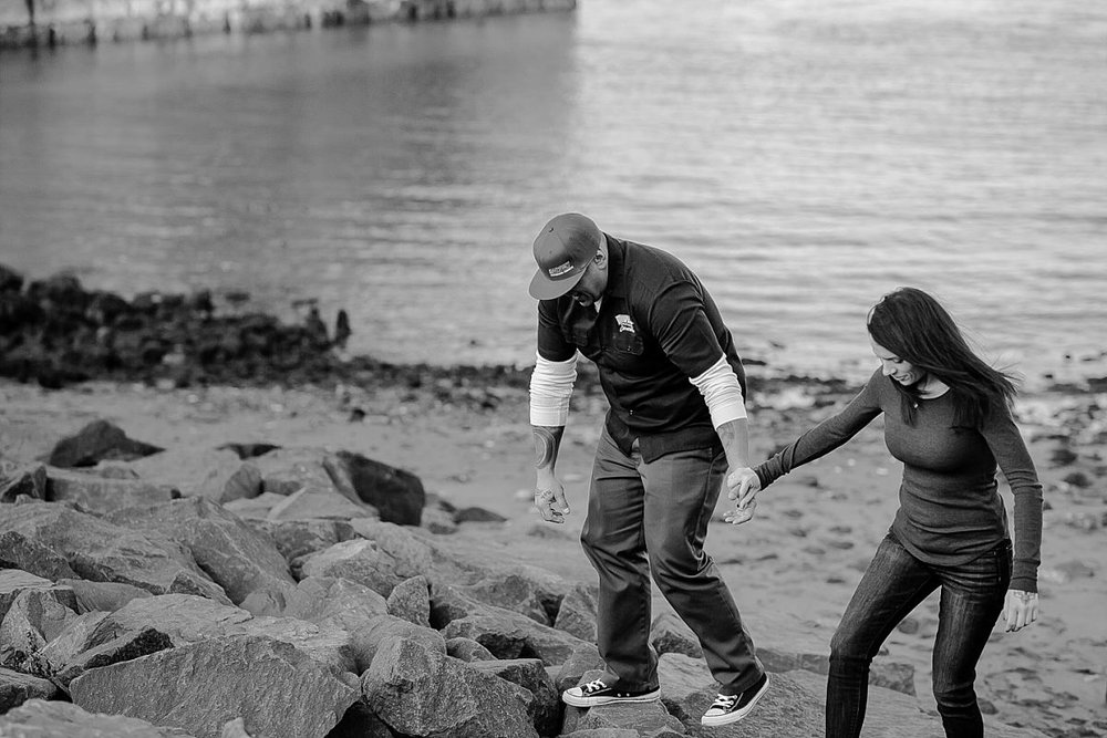 candid black and white photo of couple walking on rocks underneath the manhattan bridge in dumbo brooklyn. image by nyc family photographer krystil mcdowall