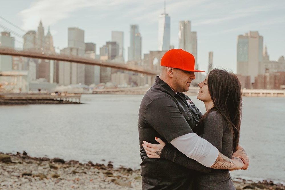 couple embraces on beach front in dumbo brooklyn looking out at beautiful manhattan skyline and brooklyn bridge. image by nyc family photographer krystil mcdowall