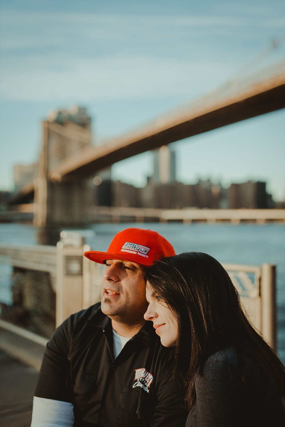 portrait of lovely couple with brooklyn bridge in the background. couple embraces on beach front in dumbo brooklyn looking out at beautiful manhattan skyline and brooklyn bridge. image by nyc family photographer krystil mcdowall