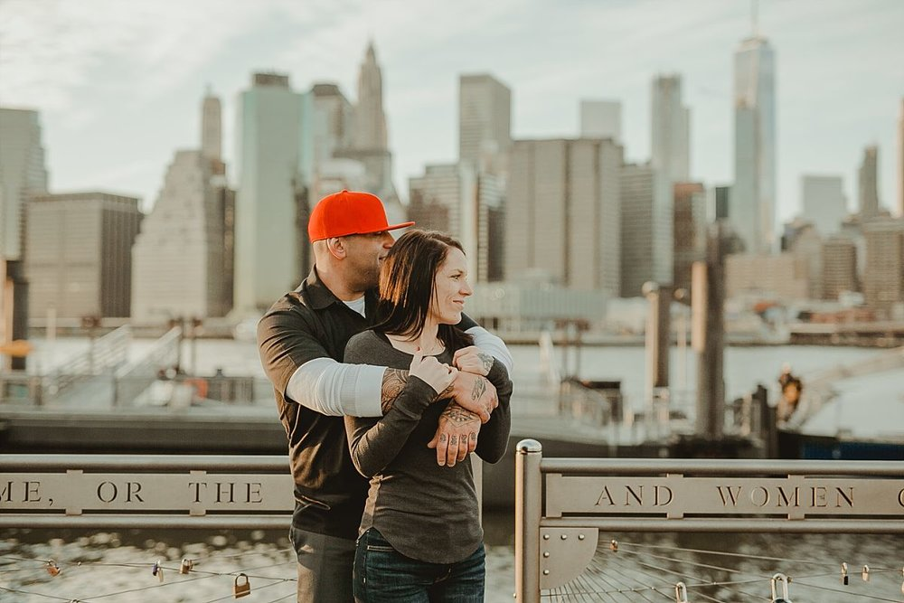 couple embraces for a quiet moment at pier in brooklyn bridge park with manhattan skyline in the background. photo by family photographer krystil mcdowall