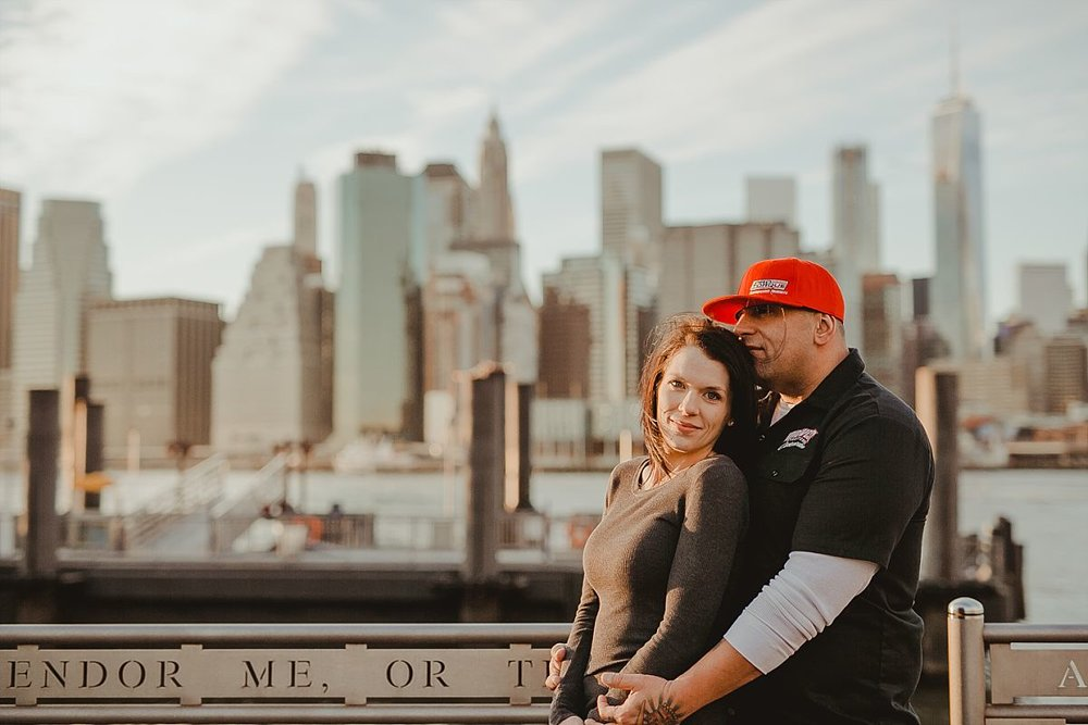 couple embraces for a quiet moment at pier in brooklyn bridge park with manhattan skyline in the background. photo by nyc family photographer krystil mcdowall