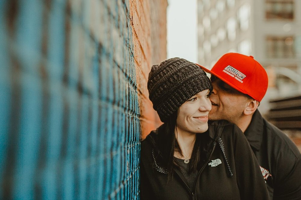 couple giggles while leaning against graffiti mural in brooklyn. photo by nyc family photographer krystil mcdowall