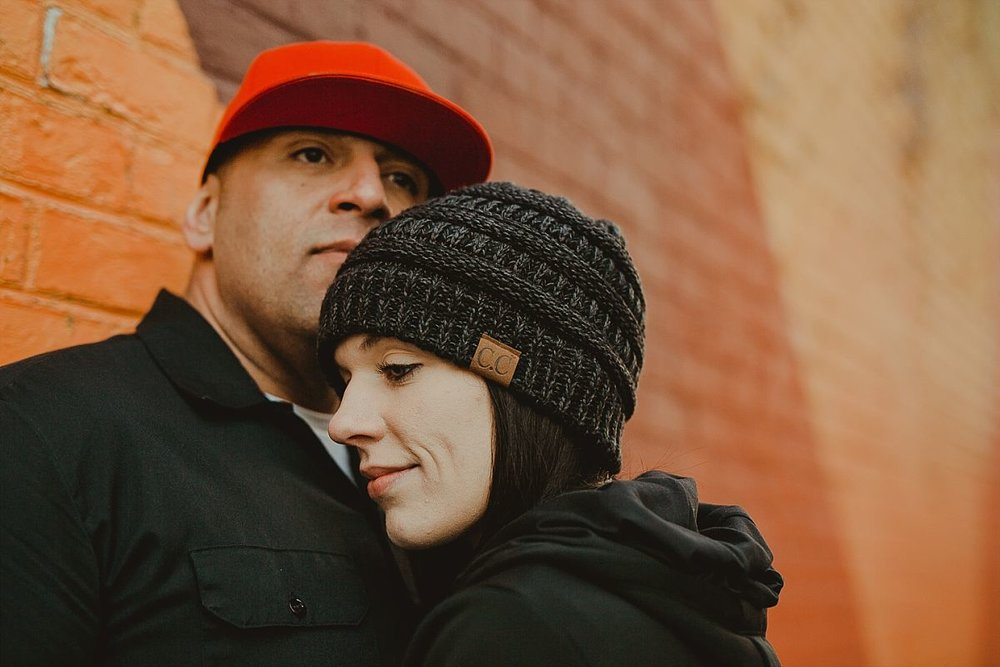 close up portrait of girlfriend leaning head on boyfriend's chest in front of orange graffiti mural in brooklyn. photo by nyc family photographer krystil mcdowall