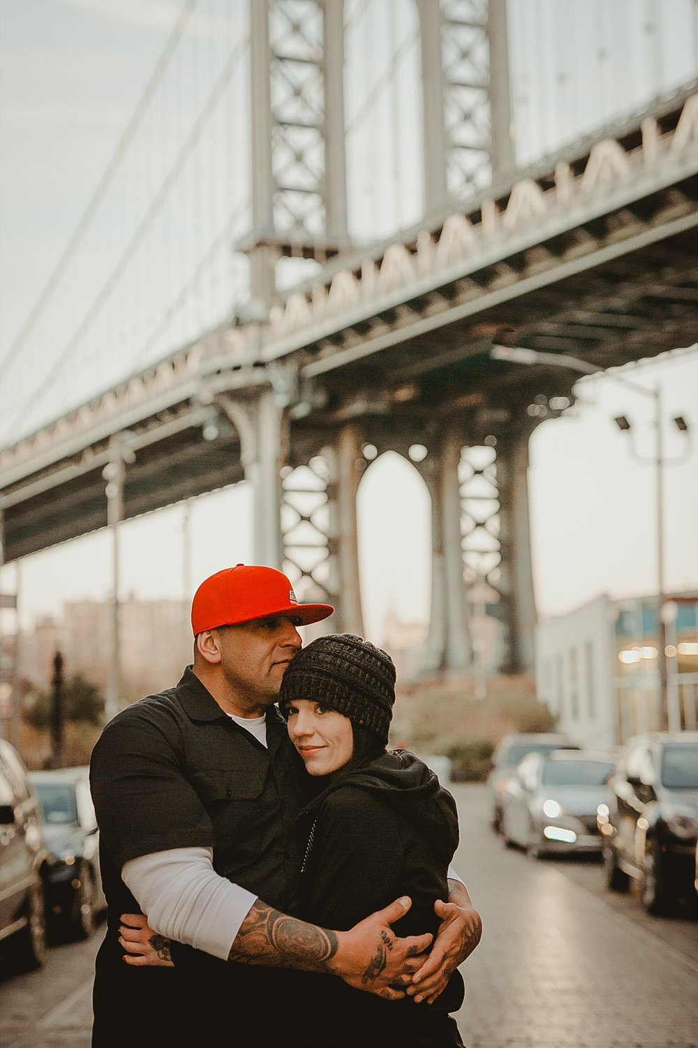 close up portrait of girlfriend leaning head on boyfriend's chest in front of manhattan bridge as sun begins to set. photo by nyc family photographer krystil mcdowall