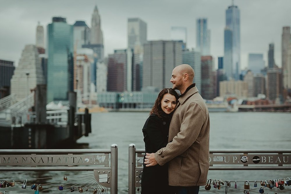 couples photo of wife looking at the camera and embracing her husband at dumbo pier with nyc skyline in the background. image by nyc family photographer krystil mcdowall