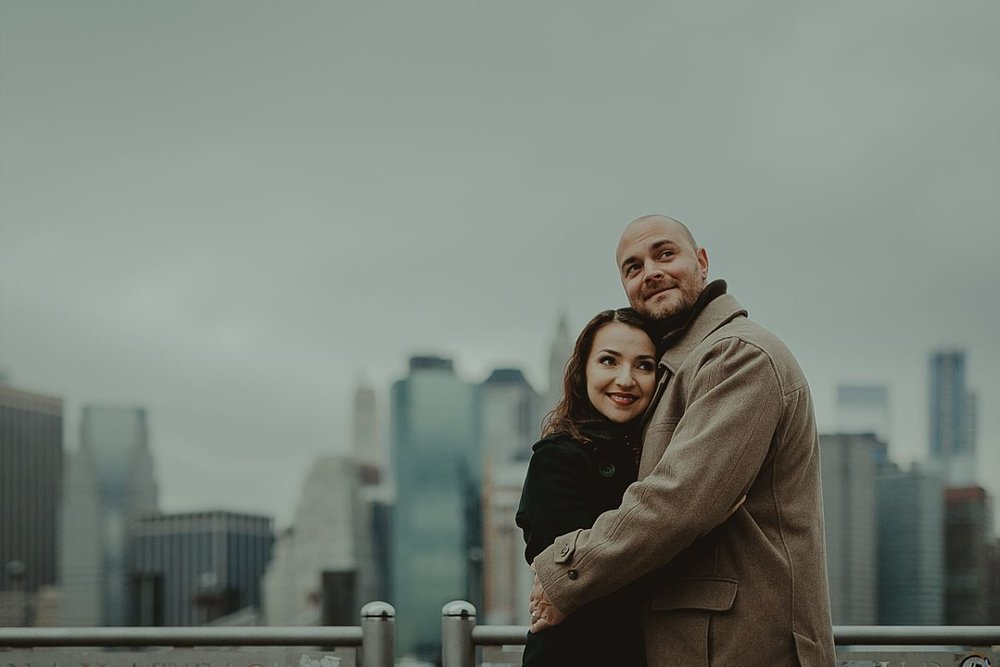 couples photo of husband and wife at dumbo pier with blurred nyc skyline in the background. image by nyc family photographer krystil mcdowall