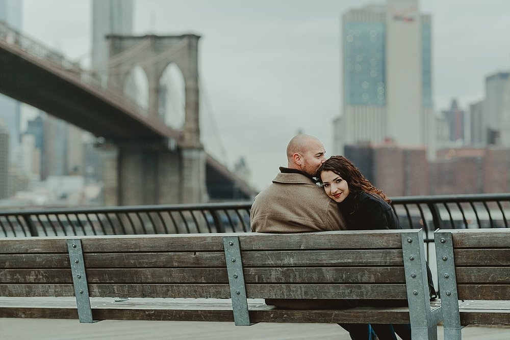 couples photo of husband and wife sitting on seat in front of the east river with the brooklyn bridge in sight. photo by nyc family photographer krystil mcdowall