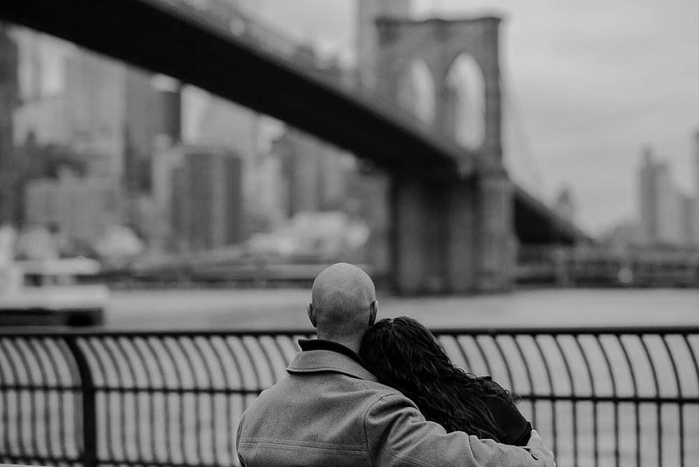 black and white photo of couple at the east river and looking out at the brooklyn bridge. image by nyc family photographer krystil mcdowall