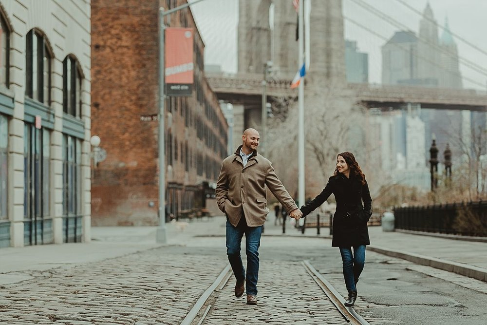 couples photo of husband and wife strolling along cobble stoned street in brooklyn hand in hand. image by nyc family photographer krystil mcdowall
