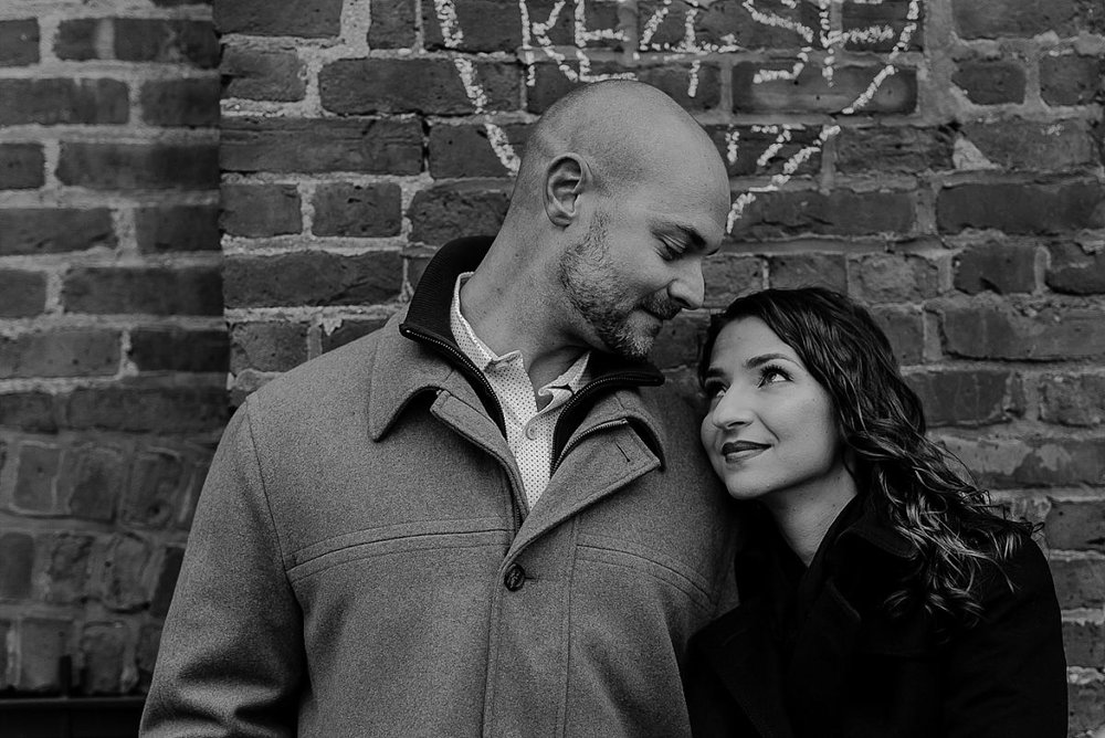close up black and white photo of married couple in front of grungy brick wall in dumbo brooklyn. image by nyc family photographer krystil mcdowall