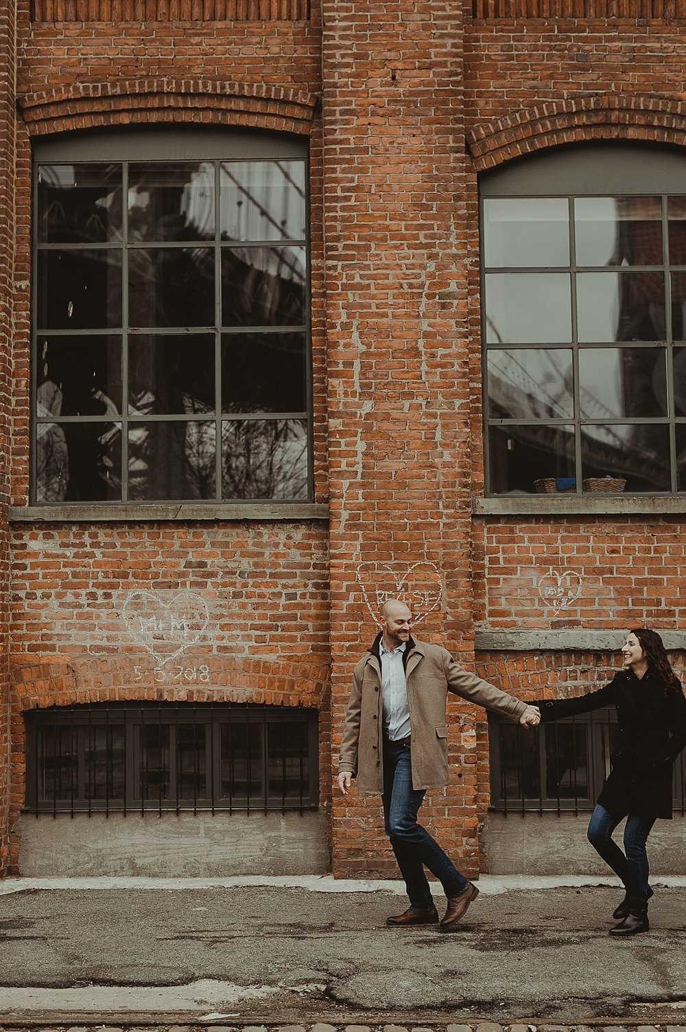 photo of married couple strolling together in front of grungy brick wall in dumbo brooklyn. image by nyc family photographer krystil mcdowall