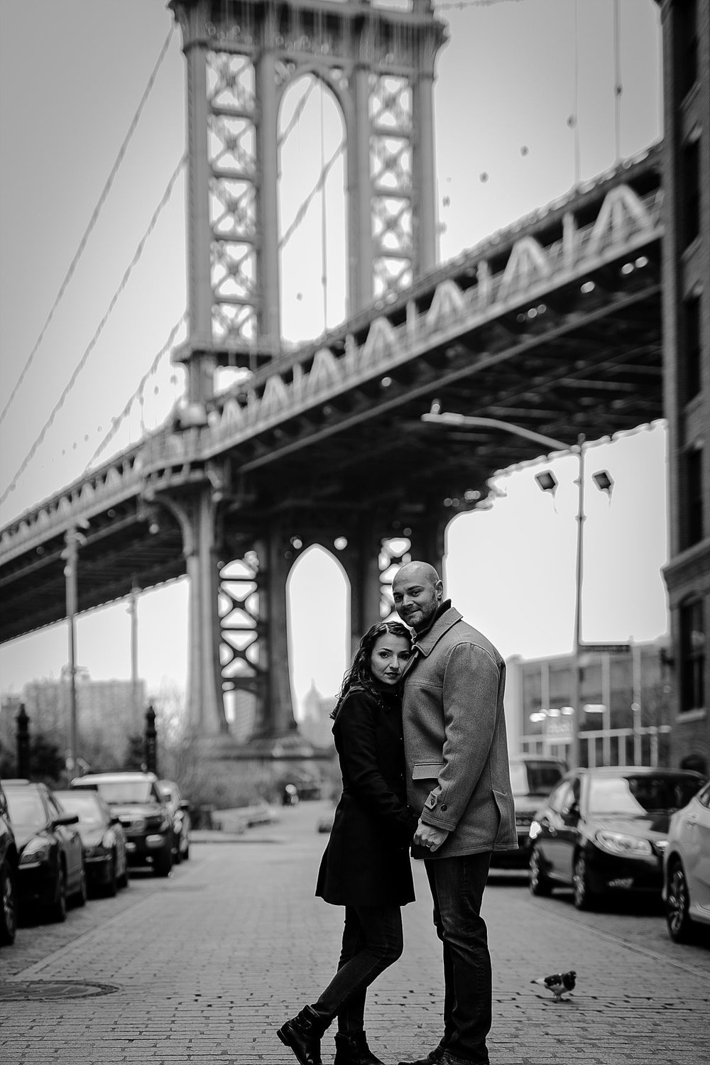 black and white couples photo of married couple in front of manhattan bridge in dumbo brooklyn. photo by krystil mcdowall photography