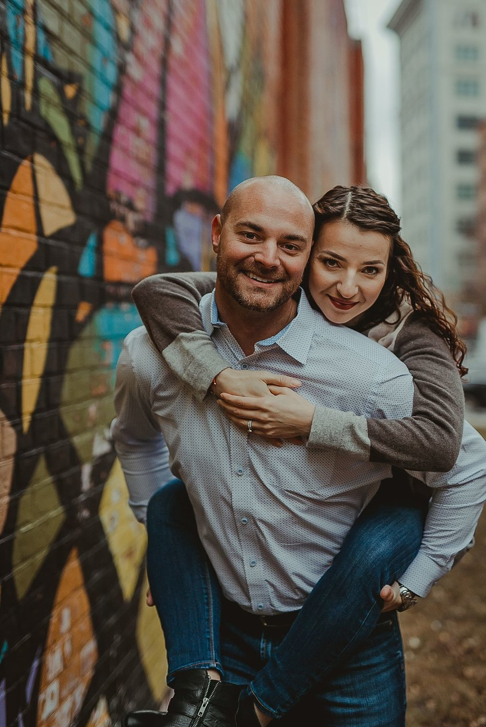 photo of husband giving wife a piggy back in front of colorful graffiti mural in dumbo brooklyn. photo by nyc family photographer krystil mcdowall