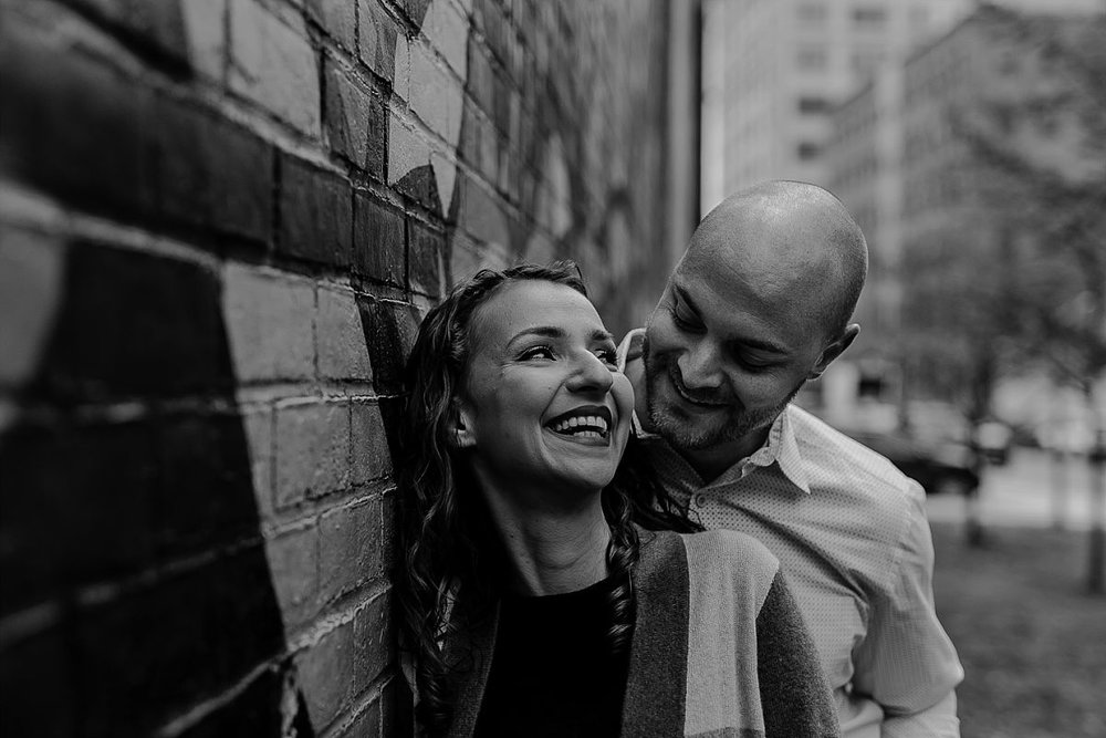 black and white photo of husband and wife giggling in front of graffiti mural in dumbo brooklyn. photo by nyc family photographer krystil mcdowall
