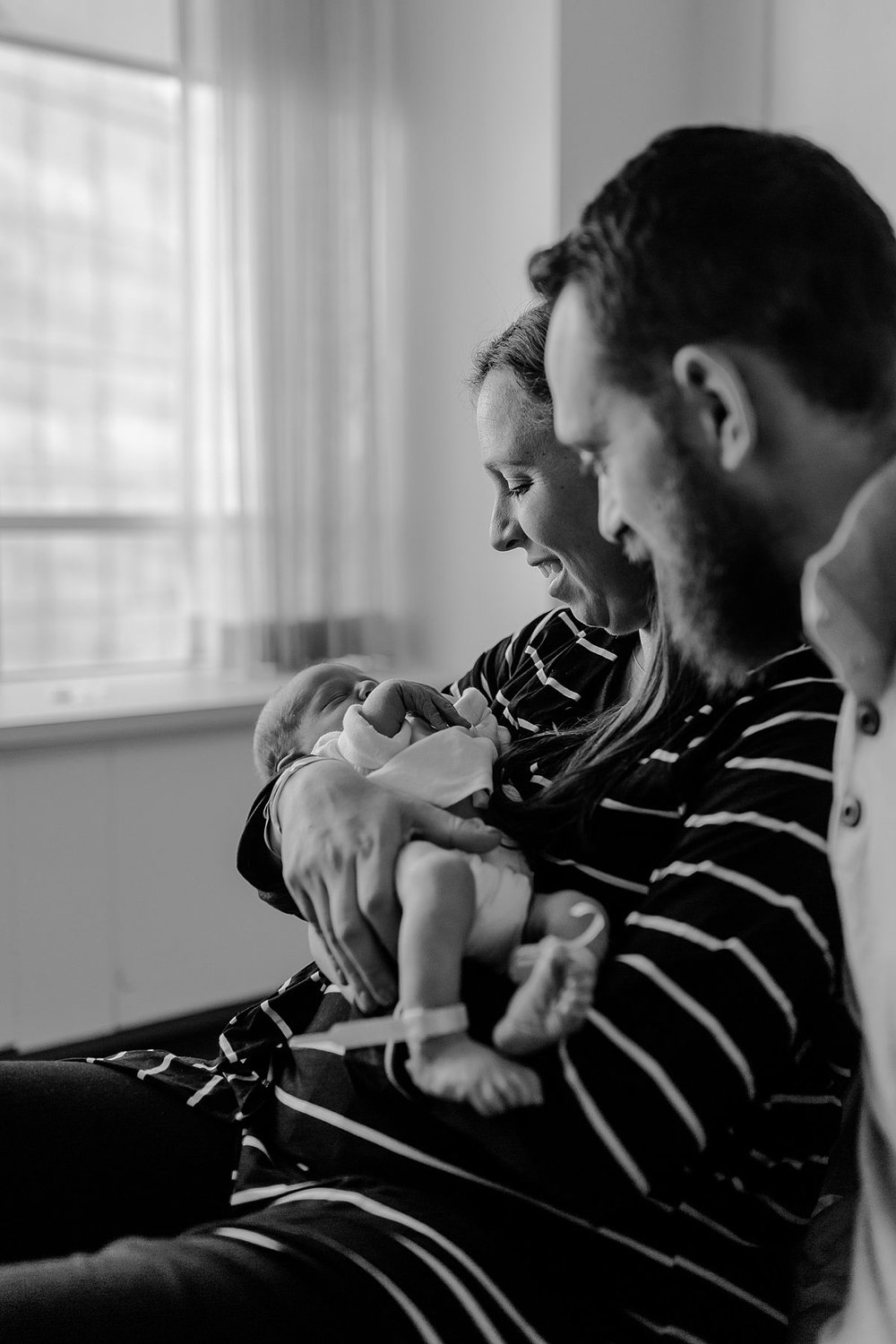 black and white fresh 48 family portrait of mom and dad smiling at newborn son. photo by nyc family and newborn photographer krystil mcdowall