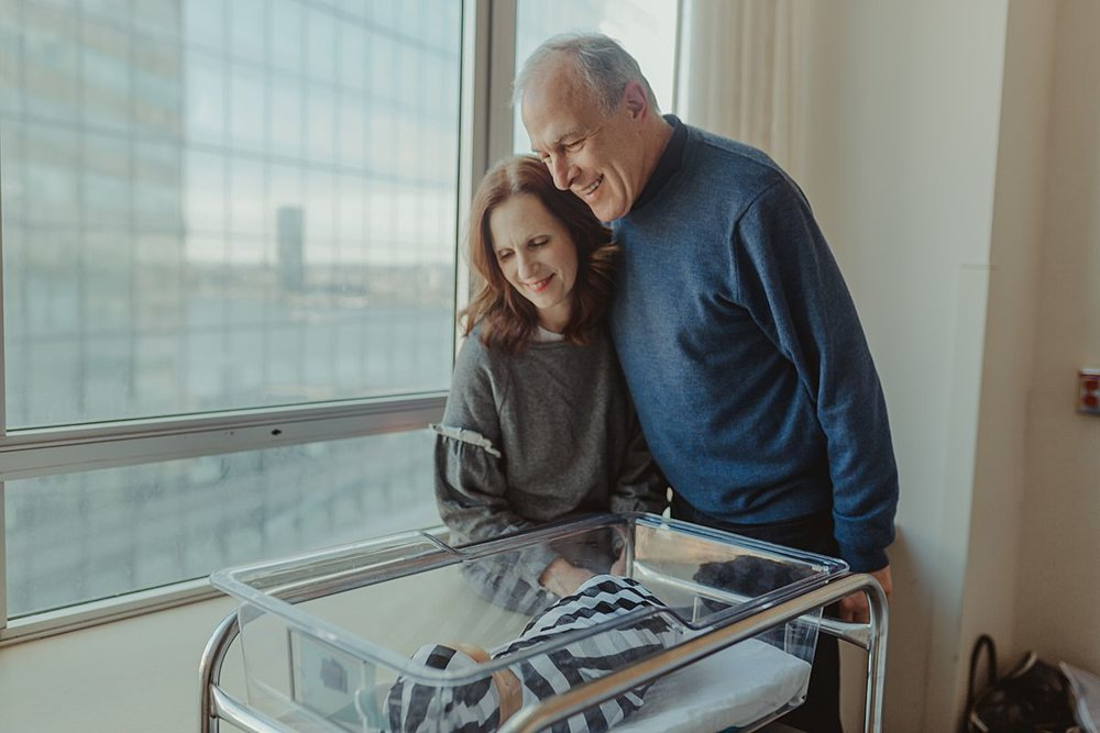 grandparents looking on as newborn grandson sleeps in his hospital bassinet. photo by nyc family and newborn photographer krystil mcdowall