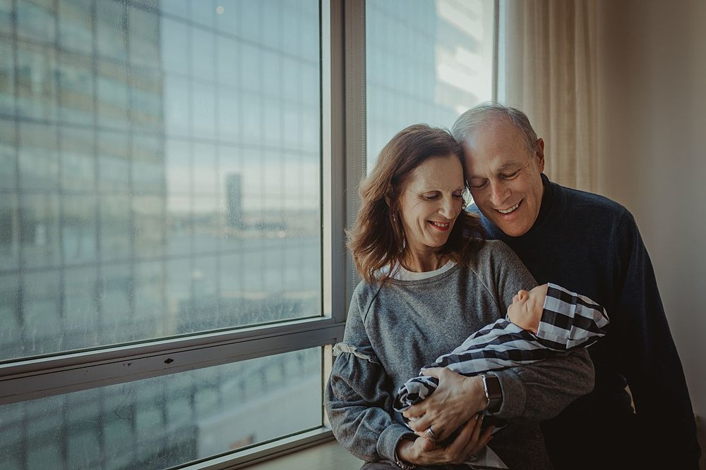 grandparents holding newborn grandson as sleeps in their arms in nyc hospital. photo by nyc family and newborn photographer krystil mcdowall