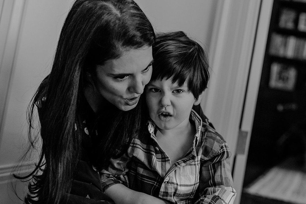 son sitting on mom's lap and making funny faces together. Capturing real family moments NYC family photographer Krystil McDowall