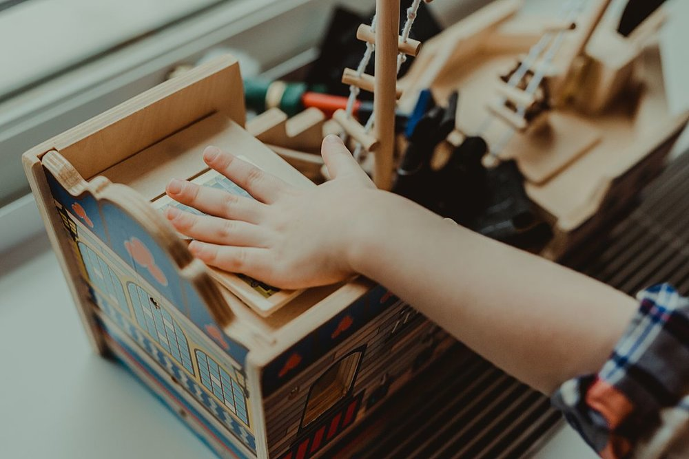 close up detail shot of young boy in room of nyc apartment playing with wooden ship toy. photo by nyc family and newborn photographer Krystil McDowall