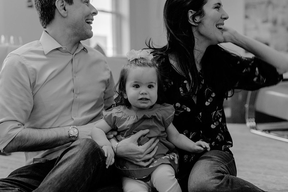 candid black and white family portrait of mom, dad and daughter playing in living room of nyc apartment. photo by nyc family and newborn photographer Krystil McDowall