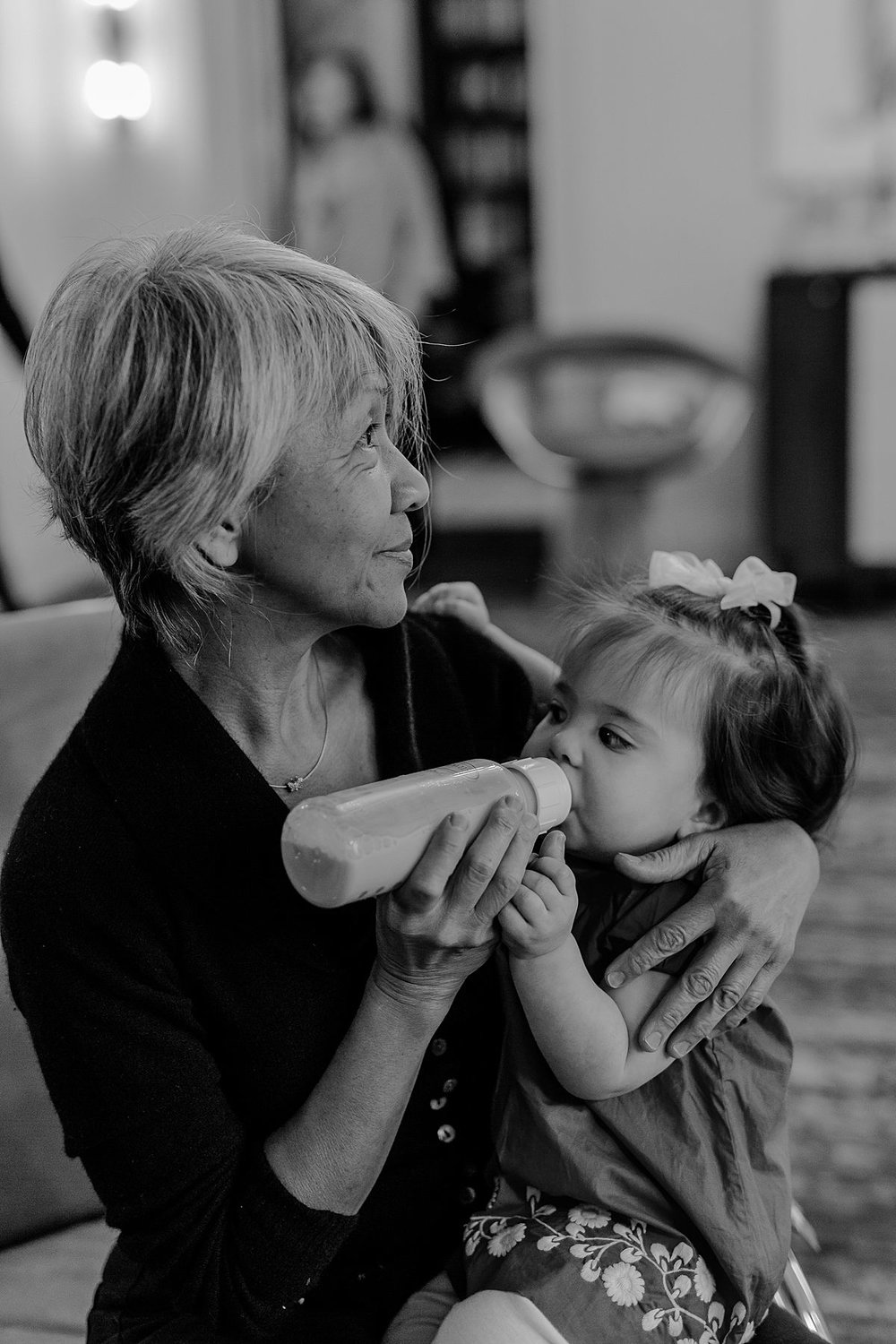 photo of nanny feeding bottle to one year old girl at her birthday party. photo by nyc family and newborn photographer Krystil McDowall