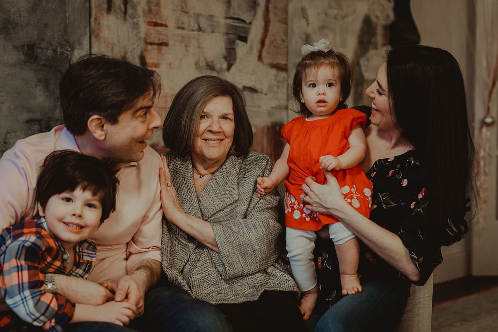 candid family portrait of one year old, big brother, mom, dad and grandmother enjoying laughter and cuddles on the couch. photo by nyc family and newborn photographer Krystil McDowall