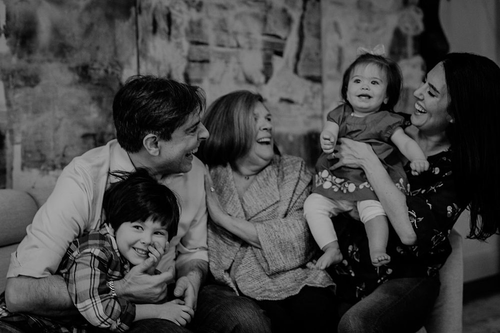 candid family portrait of one year old, big brother, dad and grandmother enjoying laughter and cuddles on the couch. photo by nyc family and newborn photographer Krystil McDowall