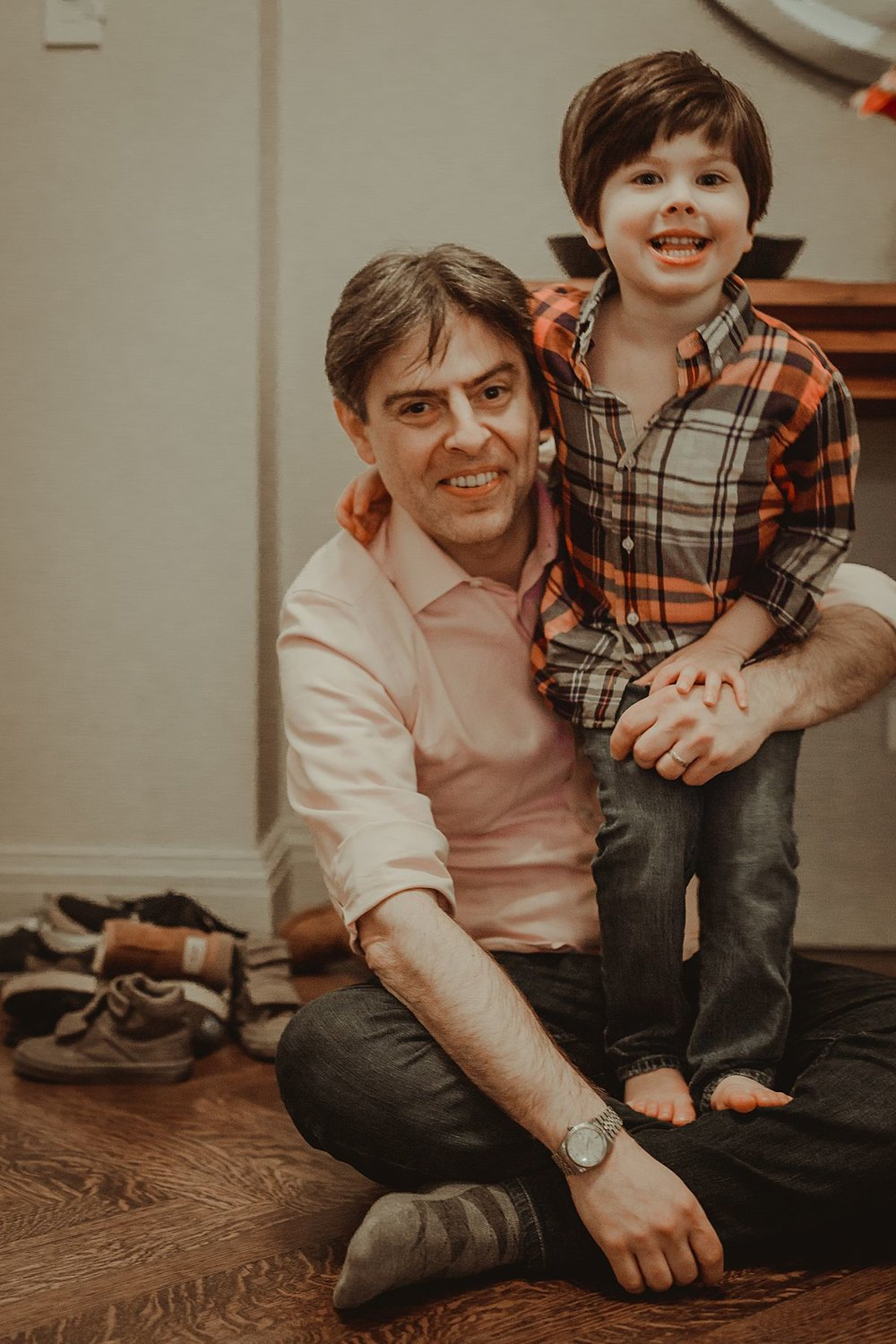dad and son portrait in nyc living room. photo by nyc family and newborn photographer Krystil McDowall