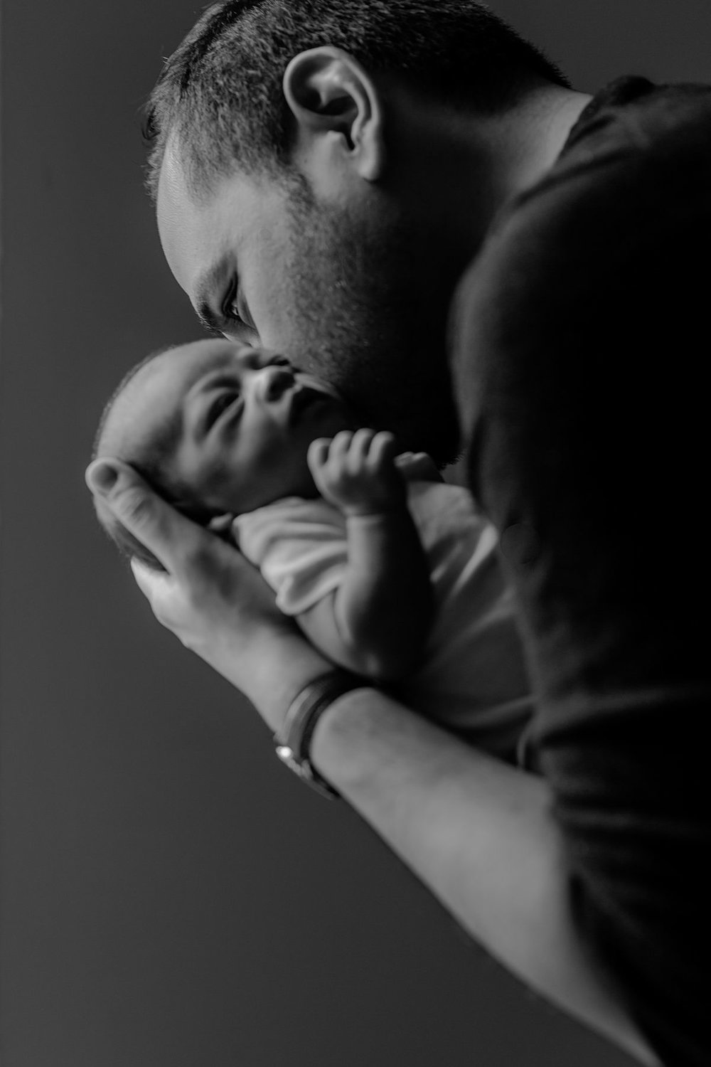 black and white portrait of dad and newborn baby boy in dad's arms near light filled window of washington heights apartment. photo by nyc family and newborn photographer krystil mcdowall