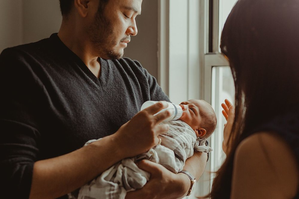 color photo of mom and dad feeding newborn baby boy near light filled window of nyc apartment. photo by nyc family and newborn photographer krystil mcdowall