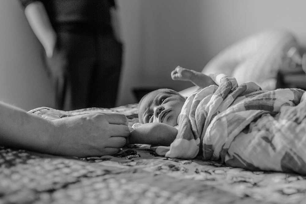 photo of mom holding newborn son's hand as he lays on parents bed and look up a his mom with big wide eyes. photo by nyc family and newborn photographer krystil mcdowall