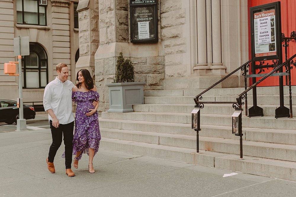 expecting couple walks in front of old church on central park west in new york city. maternity photo by nyc family and newborn photographer krystil mcdowall