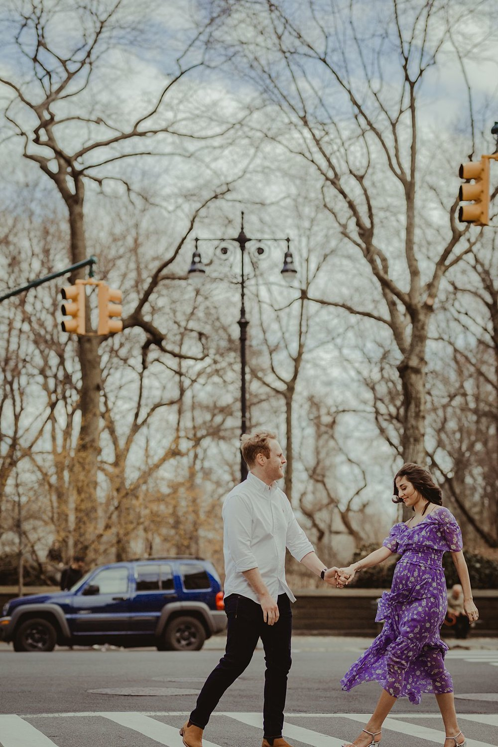 expecting couple walks along pedestrian crossing on central park west with central park in the background for maternity photo session. mom wears feminine purple and white maternity dress. photo by nyc family and newborn photographer krystil mcdowall