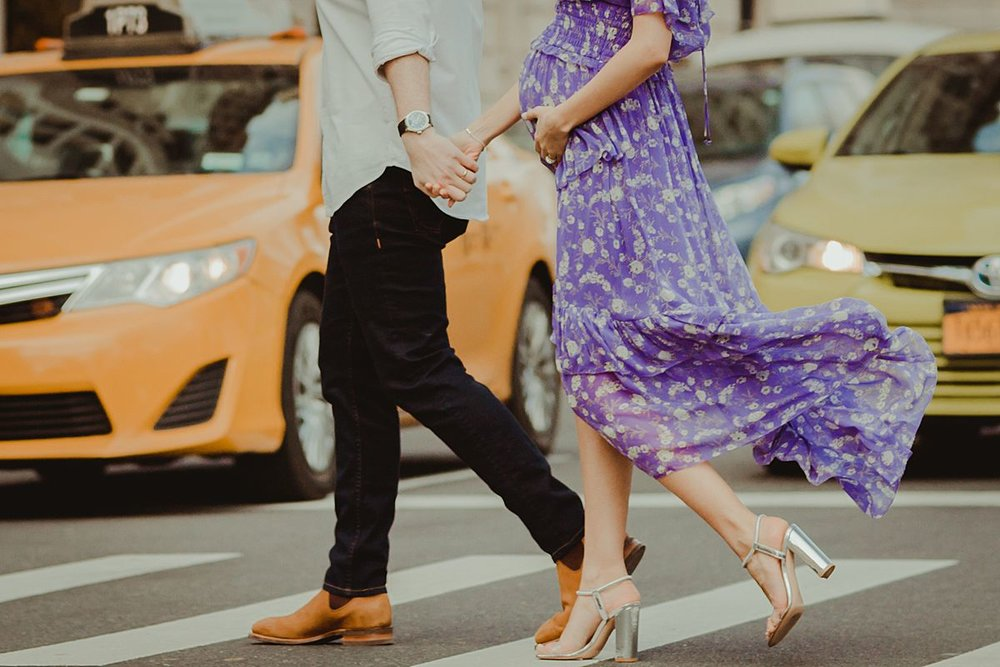 close up photo of footwear and mom's expecting belly as couple walks along pedestrian crossing at 72nd street on central park west. maternity photo by nyc family and newborn photographer krystil mcdowall