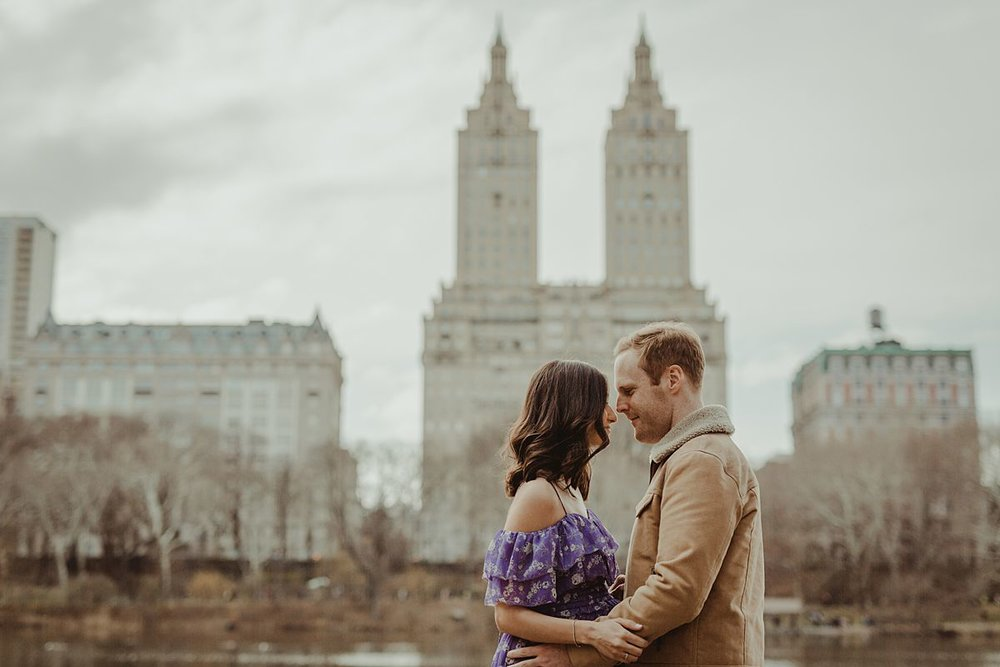 expecting couple stands in front of lake in central park with the the san remo building in the background. image by nyc family and newborn photographer krystil mcdowall