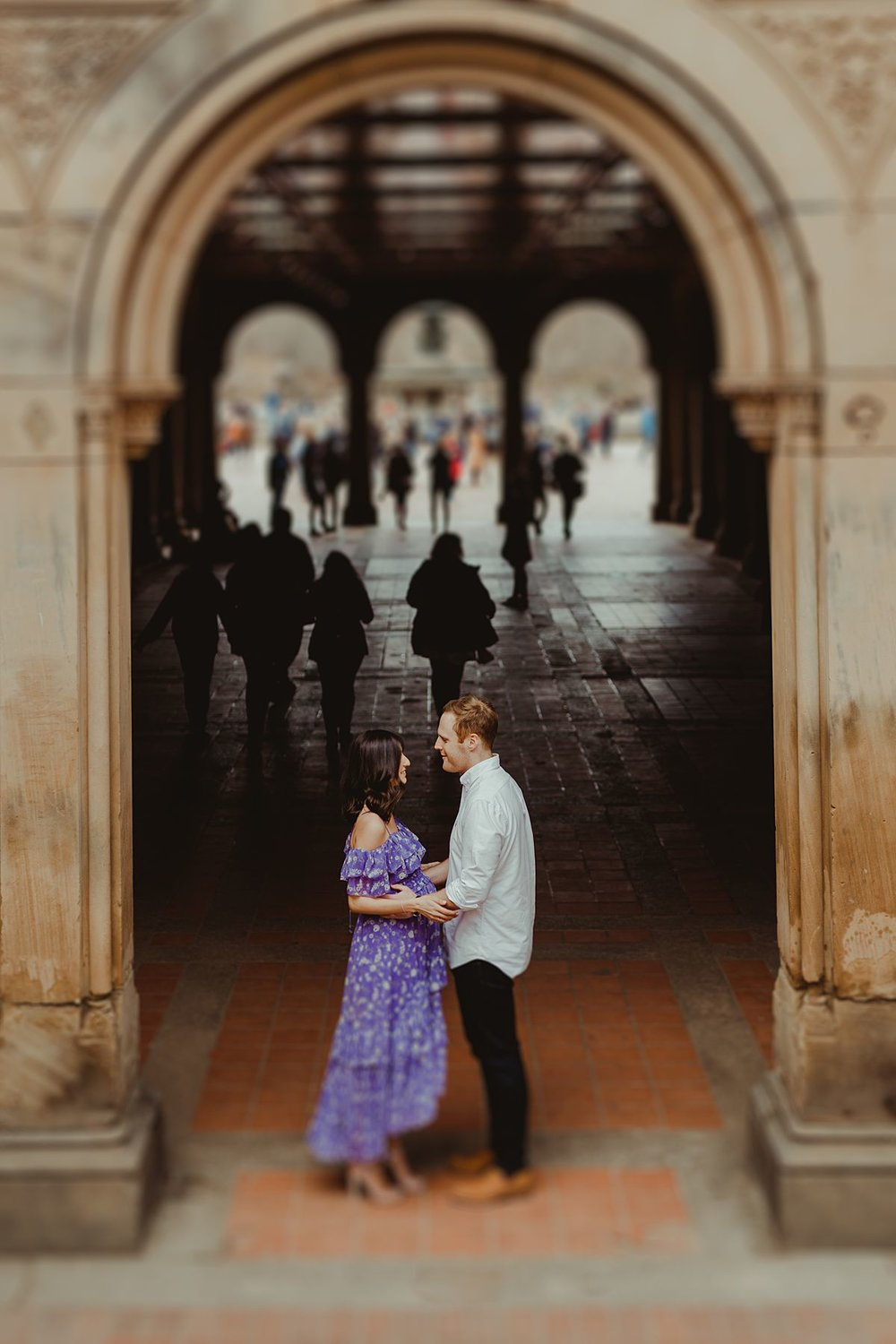 expecting couple stands at entrance to bethesda terrace in central park new york city. image by nyc family and newborn photographer krystil mcdowall