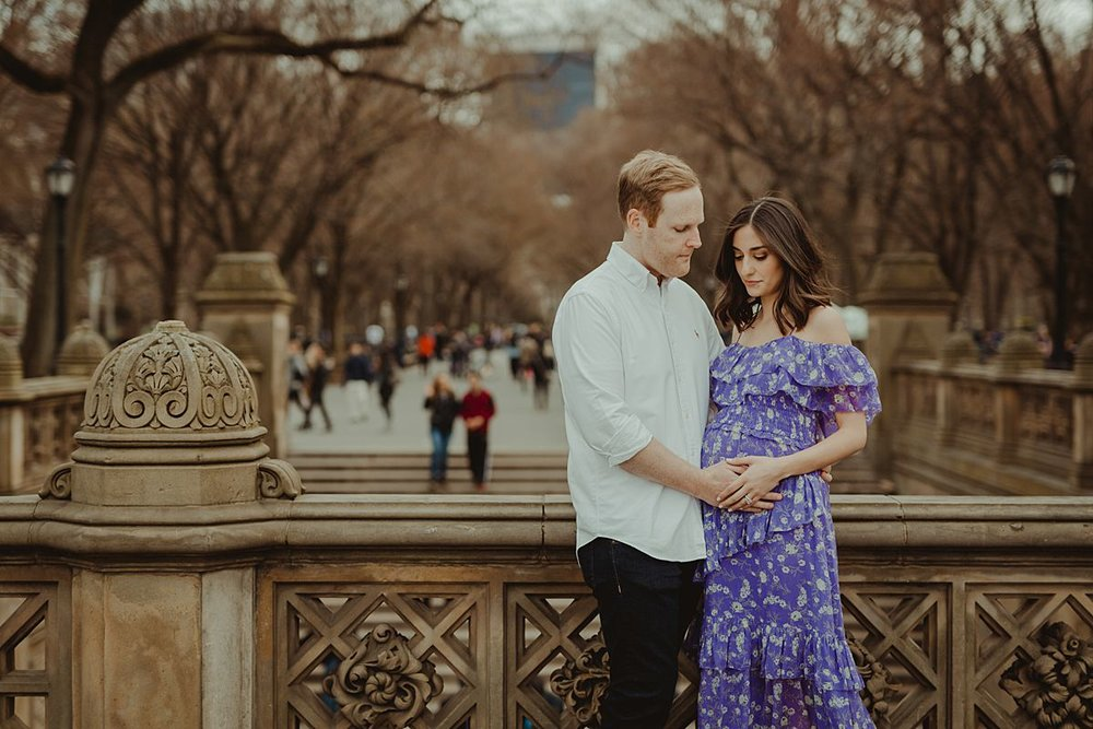 expecting couple stands at bethesda terrace in central park new york city holding mom's expecting belly. image by nyc family and newborn photographer krystil mcdowall