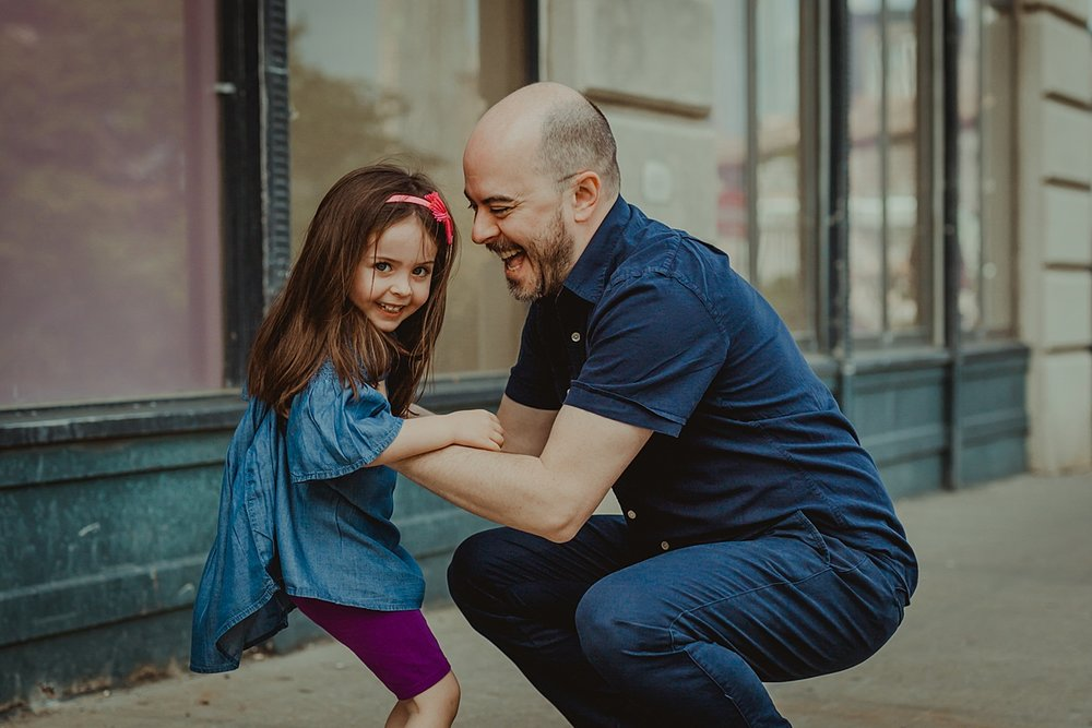 candid dad and daughter photo of the two shortly before dad throws daughter up in the air standing sidewalk in dumbo brooklyn. photo by nyc family and newborn photographer krystil mcdowall