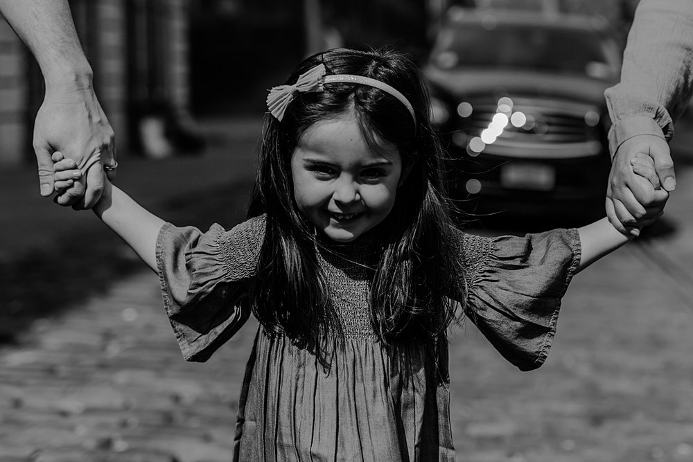 photo of young girl holding mom and dad's hands as she walks along cobble stoned street in dumbo brooklyn. photo by krystil mcdowall photography
