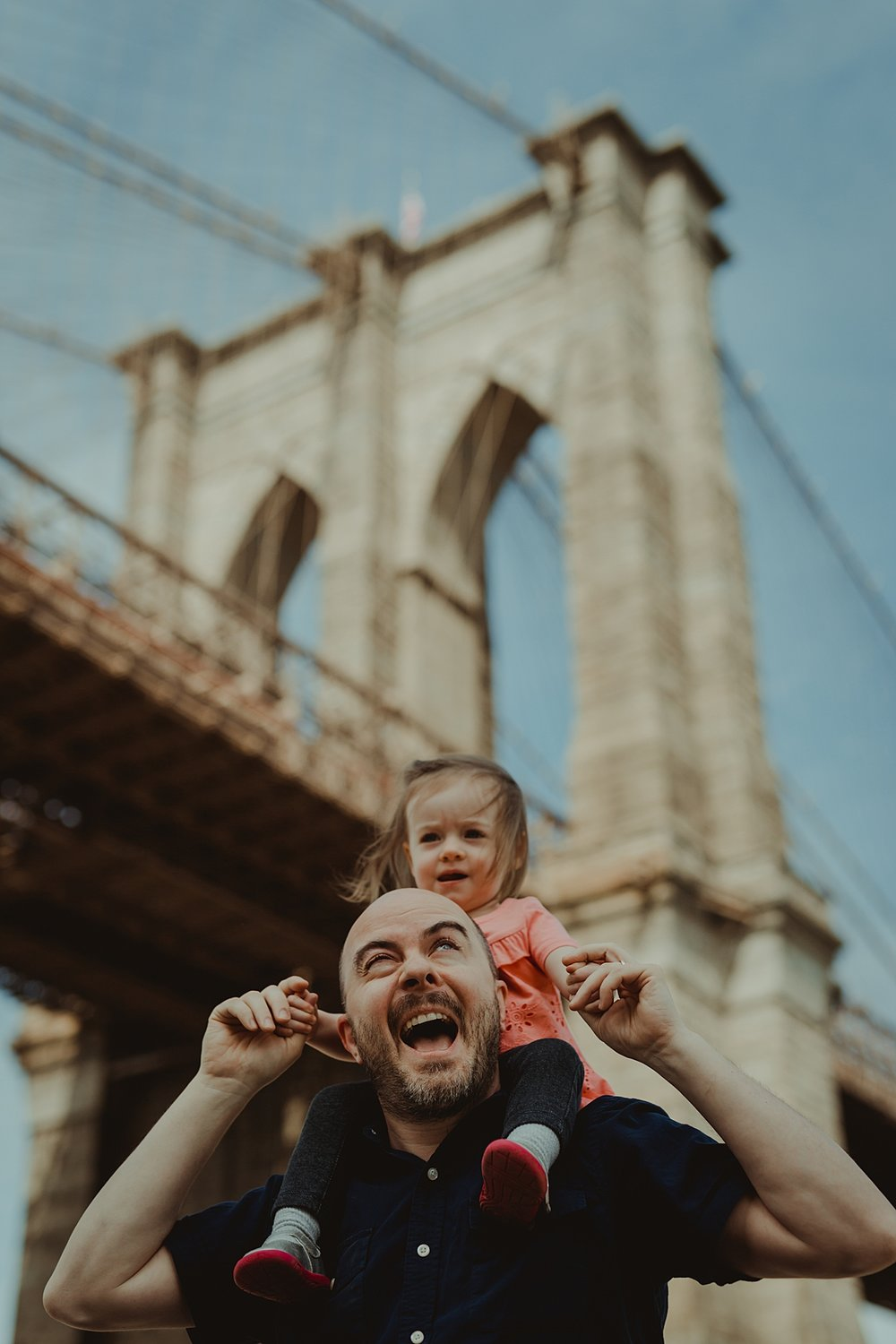 candid portrait of dad giving young daughter wearing pink shirt a shoulder ride with brooklyn bridge as the backdrop. photo by nyc family and newborn photographer krystil mcdowall