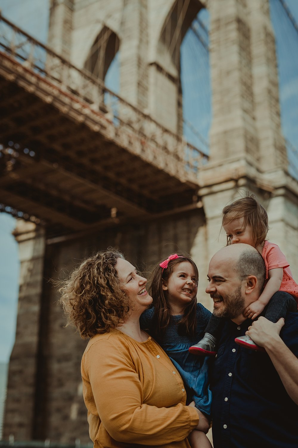 candid color portrait of family standing in dumbo with brooklyn bridge as the backdrop to family photos. photo by nyc family and newborn photographer krystil mcdowall