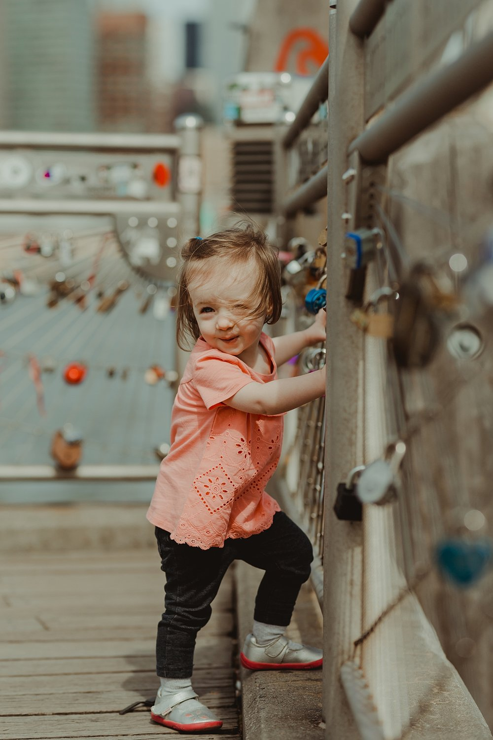 candid portrait of young daughter in pink shirt playing with the love locks at brooklyn bridge park. photo by nyc family and newborn photographer krystil mcdowall