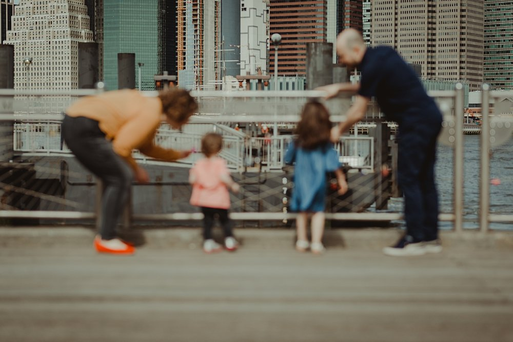 blurred family portrait of family playing with the love locks at the brooklyn bridge park with manhattan skyline as the backdrop. photo by nyc family and newborn photographer krystil mcdowall