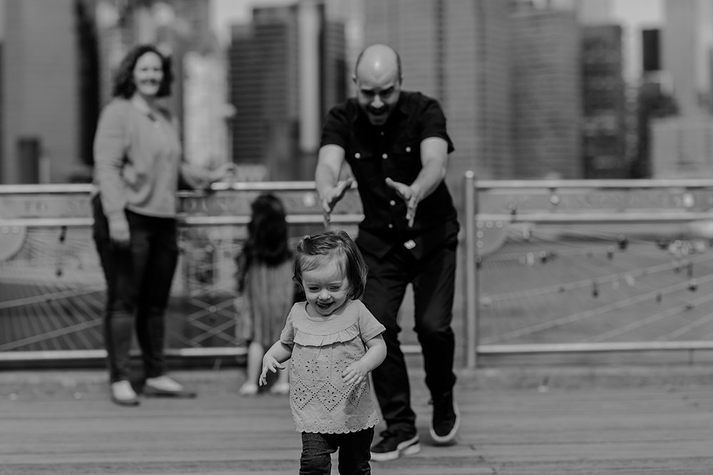 dad chasing daughter around at the pier at brooklyn bridge park with manhattan skyline in the background. photo by nyc family and newborn photographer krystil mcdowall
