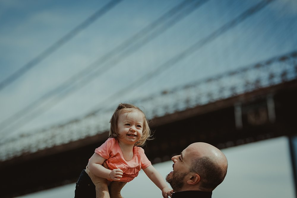 dad holding laughing daughter in the air in front of the brooklyn bridge in dumbo. photo by nyc family and newborn photographer krystil mcdowall