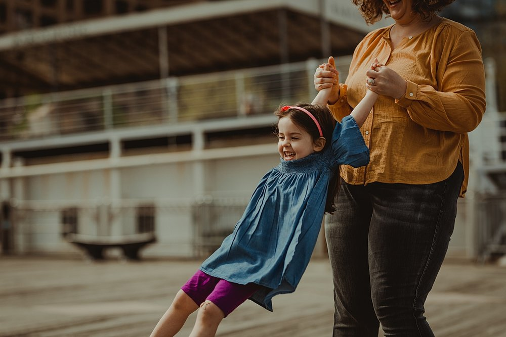 candid photo of mom spinning daughter around while she's laughing at the pier at brooklyn bridge park. photo by nyc family and newborn photographer krystil mcdowall