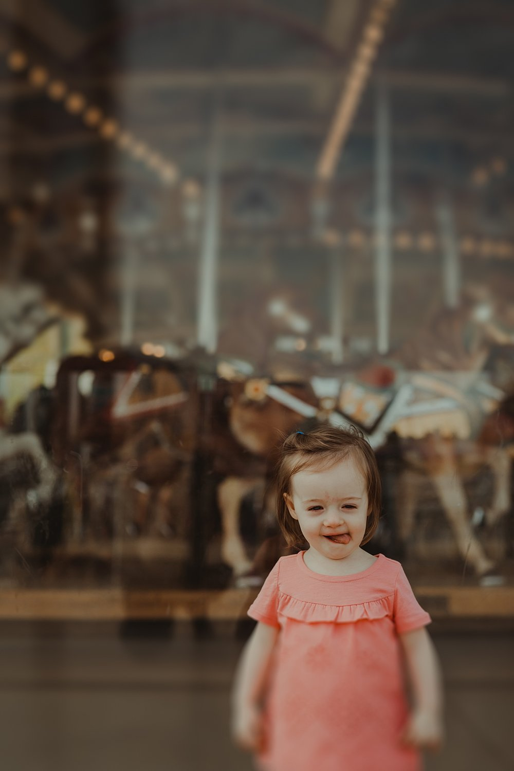 photo of daughter standing in pink shirt in front of jane's carousel in dumbo brooklyn. photo by nyc family and newborn photographer krystil mcdowall