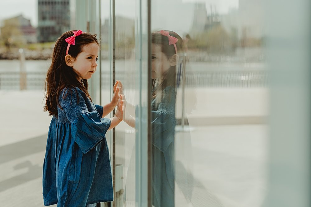photo of young girl in blue dress with pink headband standing in front of jane's carousel in dumbo brooklyn and looking in at carousel with reflection in the glass. photo by nyc family and newborn photographer krystil mcdowall