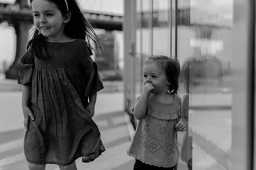 photo of two young sisters walking in front of jane's carousel in dumbo brooklyn. photo by nyc family and newborn photographer krystil mcdowall