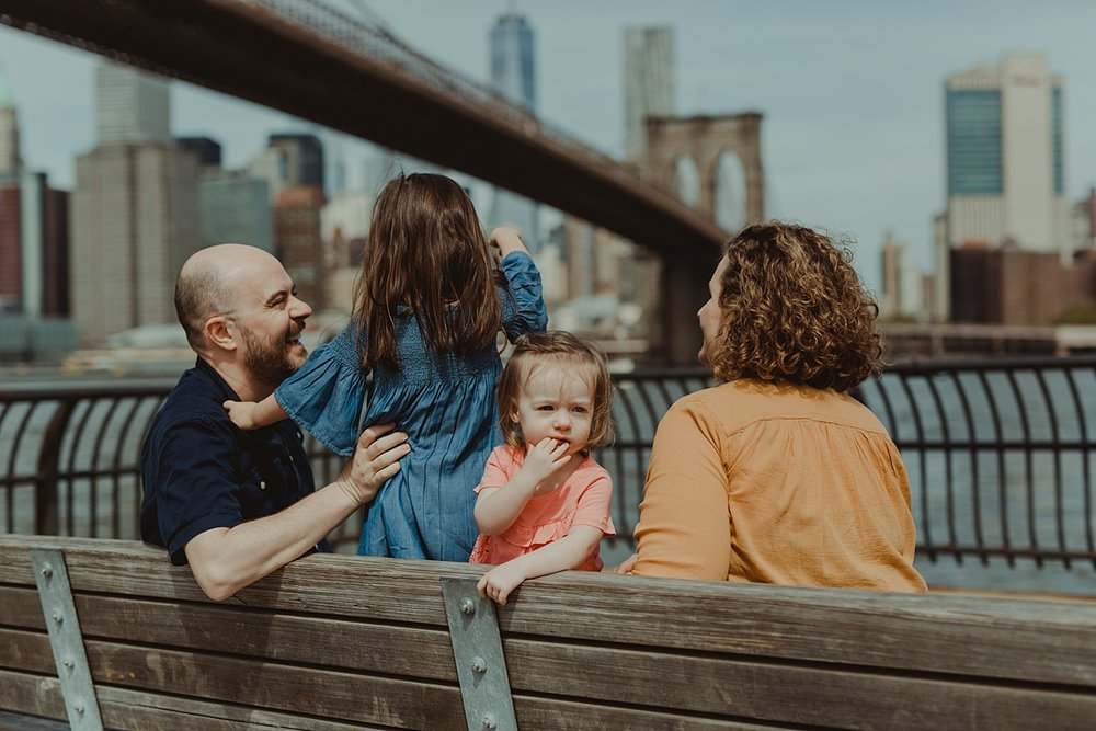 photo of family sitting on park bench with brooklyn bridge in the background. photo by nyc family and newborn photographer krystil mcdowall